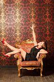 Mujer en zapatos rojos y un vestido negro sentado en una silla