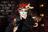 pic of witch  - Halloween witch with an unusual makeup and headdress of bats holding a mask - JPG