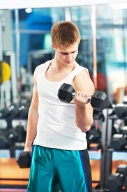 foto of triceps brachii  - athlete man workout biceps brachii muscles exercises with training dumbbell in fitness gym - JPG
