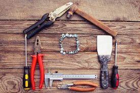 image of handyman  - Construction tools in the form of house on wooden background - JPG