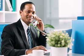 picture of indian chief  - Indian manager talking on the telephone at his workplace - JPG