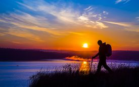 stock photo of morning sunrise  - Walking female hiker silhouette and impressive colorful sunrise on the background outdoor morning water river sky sunlight - JPG