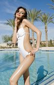 Beautiful young woman relaxing beside swimming pool on a war hot summers day