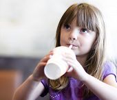 Little girl drinking soda pop out of plastic sup with straw
