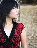 Fashion editorial profile shot of a impish pretty Asian woman,