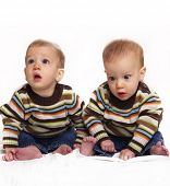 Cute adorable identical baby twin boys isolated against white background.