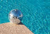Shiny silver party disco ball beside swimming pool