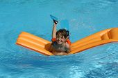young boy having fun with air bed in pool
