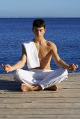 Young man doing yoga moves by the sea
