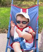 Baby In Stroller With Sunglasses And A Hat