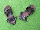 foto of splayed  - pair of used leather sandals on green astro - JPG