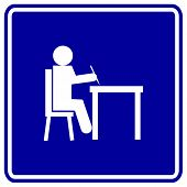 student writing in desk sign
