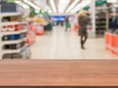 Wooden Empty Table In Front Of Blurred Supermarket poster