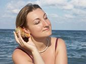 Young woman in bikini at the beach putting sea shell up to her ear and listening its murmur