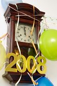 Wooden wall clock decorated with streamers, balloons and 2008 year figures showing almost New Year time
