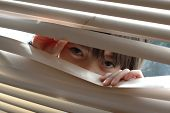 Little girl behind venetian blind