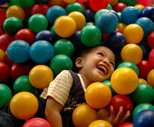 Little boy having fun time in balls pool