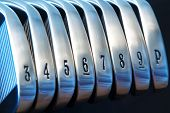 A brand new set of golf club irons poster