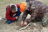 HUnter education instructor teaching fire starting survival technique to student