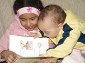 foto of storytime  - baby and big sister reading a book - JPG