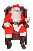 Santa sitting and enjoying a rest after a nights work, with a small libation, isolated on white