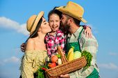 Parents And Daughter Farmers Celebrate Harvest Holiday. Family Farmers Hug Kiss Kid Hold Basket Fall poster