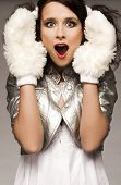 beautiful brunette winter girl wearing furry gloves and white dress on light background