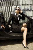 attractive brunette businesswoman in a cabrio car