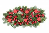 Christmas table decoration with red bauble decorations, winter flora of holly berries, snow covered  poster