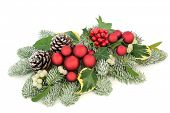 Christmas table decoration with red bauble decorations, holly berries, snow covered spruce pine, ivy poster