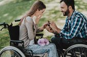 Man On Wheelchair Makes Marriage Proposal In Park. Disabled Young Man. Woman On Wheelchair. Date In  poster