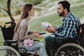 Couple Of Disabled People Exchanging Gifts In Park. Disabled Young Man. Woman On Wheelchair. Date In poster