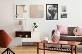 Real Photo Of White Sitting Room Interior With Poster On Wall, Couch With Cushions And Blanket, Wood poster