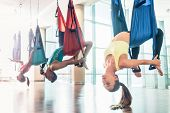Side view of a fit and beautiful young woman hanging upside down while practicing aerial yoga during poster