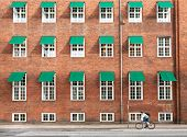 Cyclist Driving Past Old Brick House With Many Windowds In Historical Area Of Copenhagen, Denmark. O poster