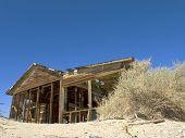 Casa velha abandonada rodeada por um lindo céu azul e as areias do deserto. Decomposição de estruturas de madeira Soares