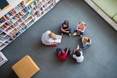 Teacher reading fairy tales to children sitting in a circle at library. Top view of librarian sittin poster