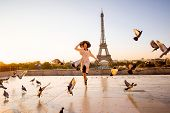 Woman Running On The Famous Square Dispersing Pigeons With Great View On The Eiffel Tower Early In T poster