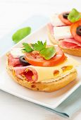Sandwiches with salami, cream cheese, tomatoes, camembert, black olives, fresh parsley and basil ser poster
