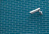 Security camera on the brick wall of a building