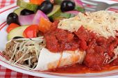 stock photo of enchiladas  - Closeup of an enchilada topped with tomato sauce and cheese - JPG