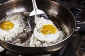pic of grease  - Eggs in frying pan being cooked by bacon grease with spatula - JPG
