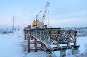 stock photo of night crawler  - The cost of removing the old bridge on a winter evening - JPG