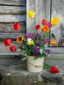 picture of flower-arrangement  - Flower arrangement including tulips displayed in bucket on stone steps - JPG