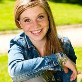 Joyful young girl enjoying sunshine outdoors wearing denim jacket