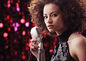 picture of singer  - Young female singer with brown curly hair singing a song - JPG