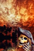 stock photo of plunder  - Pirate skeleton in the caribbeans at dusk - JPG