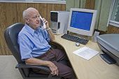 picture of senior-citizen  - Senior Citizen talks on phone in modern office - JPG