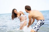 Beach summer fun couple playful splashing water together laughing playing during summer holidays vacation on tropical beach. Beautiful young interracial multiracial couple, Asian woman, Caucasian man.