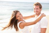image of multicultural  - Happy couple on beach in love having fun holding around each other hugging looking at camera - JPG